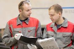 Lavoratori industriali di fabbricazione che riflettono nell'officina della fabbrica immagine stock libera da diritti