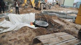 Lavoratori lenti in caschi in fossa con il materiale del panno al cantiere archivi video