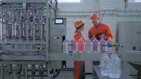 Lavoratori maschio e donna di industria nel casco e nelle tute vicino alla linea del trasportatore per acqua minerale imbottiglia video d archivio