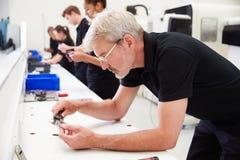 Lavoratori nell'industria meccanica che controllano qualità componente fotografie stock
