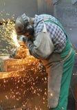 Lavoratori nelle colate di una frantumazione della fonderia con una macchina per la frantumazione - lui immagini stock libere da diritti