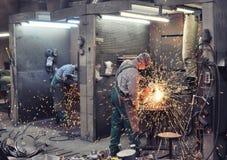 Lavoratori nelle colate di una frantumazione della fonderia con una macchina per la frantumazione - lui fotografia stock libera da diritti