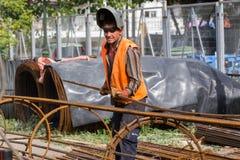 Lavoratori non identificati che lavorano con il ferro concreto ad un constructio Immagini Stock