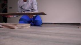 Lavoratori professionisti che pongono i bordi di legno del laminato della quercia sul pavimento nella nuova stanza archivi video