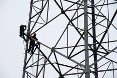 lavoratori sul palo di energia Una griglia del palo recentemente installato di energia con gli impiegati Fotografia Stock