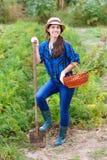 Lavoratrice agricola con la vanga ed il canestro delle verdure raccolte Fotografia Stock Libera da Diritti