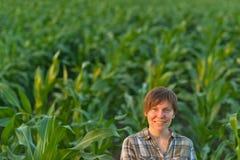 Lavoratrice agricola nel campo di grano verde Immagine Stock