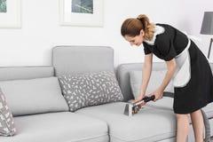 Lavoratrice che rimuove sporcizia dal sofà con l'aspirapolvere professionale, all'interno fotografia stock libera da diritti
