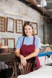 Lavoratrice che sorride mentre appoggiandosi sedia dentro Fotografia Stock Libera da Diritti