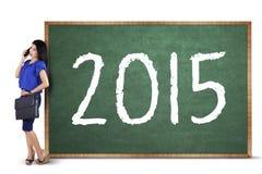 Lavoratrice con i numeri 2015 sulla lavagna Immagini Stock Libere da Diritti