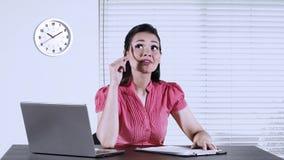 Lavoratrice con il computer portatile in posto di lavoro stock footage