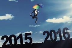 Lavoratrice con l'ombrello che salta sul cielo Immagine Stock
