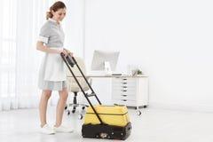 Lavoratrice con la macchina di pulizia del pavimento, all'interno fotografie stock