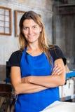 Lavoratrice con sorridere attraversato armi in carta Immagini Stock