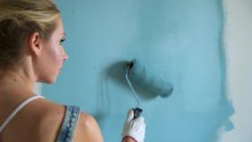 Lavoratrice facendo uso del rullo in un secchio per dipingere le pareti nell'appartamento o nella casa Costruzione, riparazione e archivi video