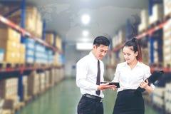 Lavoratrice uomo di affari ed asiatici di affari in magazzino facendo uso di fotografie stock