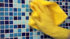 Lavoretti della Camera - pulire la parete del bagno con il panno di pulizia e lo spr video d archivio