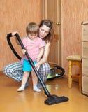 Lavoretti della figlia e della madre con l'aspirapolvere Fotografie Stock