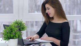 Lavori ad Internet, computer portatile di usi dell'impiegato di concetto ed apre il taccuino sul lavoro