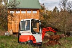 Lavori al cantiere di una casa ecologica L'escavatore regola il terreno Un piccolo zappatore nel giardino Fotografia Stock Libera da Diritti