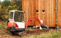 Lavori al cantiere di una casa ecologica L'escavatore regola il terreno Un piccolo zappatore nel giardino Immagini Stock Libere da Diritti