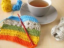 Lavori all'uncinetto il lavoro e una tazza di tè Fotografie Stock