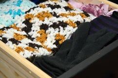 Lavori all'uncinetto le sciarpe ed i guanti in cassetto Fotografie Stock