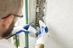 Lavori di costruzione Isolamento della schiuma di stirolo della costruzione Il lavoratore rimuove i pezzi di polistirolo Immagini Stock Libere da Diritti