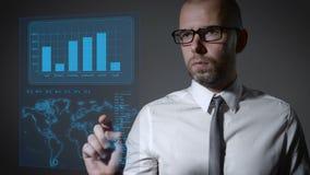 Lavori futuri con economia di macro e di finanza Uomo d'affari che lavora con uno schermo olografico interattivo video d archivio