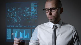 Lavori futuri con economia di macro e di finanza Uomo d'affari che lavora con uno schermo olografico interattivo stock footage