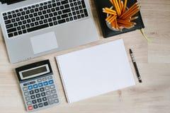 Lavori la tavola della scrivania con il computer portatile, riduca in pani, rifornimenti e calcolatore Vista superiore con lo spa Fotografia Stock Libera da Diritti