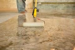 Lavori laccando i pavimenti di calcestruzzo facendo uso del rullo per ricoprire immagine stock libera da diritti