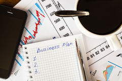 Lavori nell'ufficio, tazza di caffè con il business plan Immagine Stock