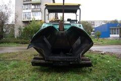 Lavori a porre la pavimentazione dell'asfalto su una via occupata della città Macchina per la stenditura della pavimentazione immagine stock libera da diritti