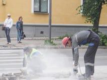 Lavori a porre le nuove mattonelle su una via della città Pone le nuove mattonelle sul pavimento Pavimentando nella città Abbelli immagine stock