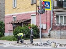 Lavori a porre le nuove mattonelle su una via della città Pone le nuove mattonelle sul pavimento Pavimentando nella città Abbelli fotografia stock