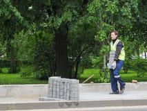 Lavori a porre le nuove mattonelle su una via della città Pone le nuove mattonelle sul pavimento Pavimentando nella città Un uomo Fotografie Stock Libere da Diritti