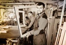 Lavori professionali maschii premurosi con i profili finiti del PVC Immagine Stock