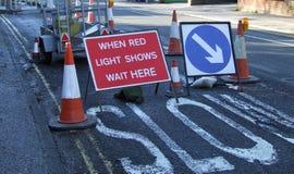 Lavori stradali con quando gli spettacoli di luci rossi aspettano qui il segno fotografia stock