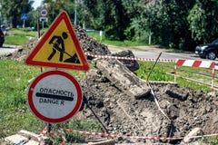 Lavori stradali sulla via della città Lavoro stradale e segnali di pericolo Immagine Stock Libera da Diritti