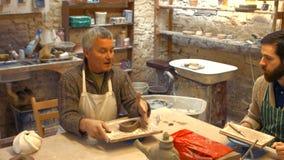 Lavoricchii insegnando al suo collega a modellare l'argilla archivi video