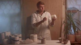 Lavoricchii, officina dell'argilla, il concetto di arte della ceramica - l'uomo castana stante vestito in un grembiule, mani masc video d archivio