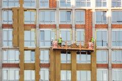 Lavoro ad alta altitudine sulle pareti esterne di grattacielo Isolamento della lana di vetro Fotografie Stock