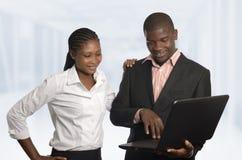 Lavoro africano del socio commerciale sul taccuino Immagini Stock