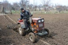 Lavoro agricolo della primavera Agricoltore su un trattore nel campo Fotografie Stock Libere da Diritti