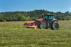Lavoro agricolo Trattore rosso che falcia il prato, repubblica Ceca L'agricoltore ha raccolto il fieno Fotografia Stock
