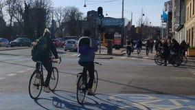 Lavoro andante dei cittadini di Copenhaghen in automobili e biciclette, ora di punta sulla via ammucchiata archivi video