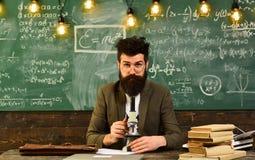 Lavoro barbuto dell'uomo con il microscopio Uomo con la barba e baffi a scuola Lo scienziato fa la ricerca sulla lavagna Fotografia Stock Libera da Diritti