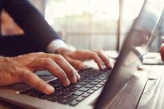 Lavoro con il computer portatile ed il pc aperti facendo uso di Immagine Stock