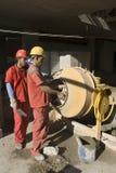Lavoro con il miscelatore di cemento - verticale degli uomini Immagini Stock Libere da Diritti